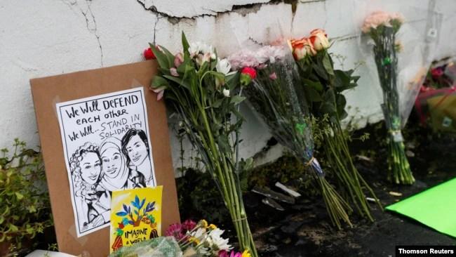 人们枪击地点摆放鲜花哀悼亚特兰大连环枪击案中遇难者。(2021年3月18日)