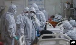 Seorang dokter berbicara melalui interkom dengan konsultan senior memberikan informasi terbaru tentang pasien di rumah sakit khusus untuk perawatan pasien COVID-19 terbesar di Mumbai, India, Kamis, 6 Mei 2021. (AP Photo / Rafiq Maqbool)