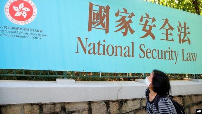 香港一名妇女走过街头的国安法宣传牌。(2020年6月30日)