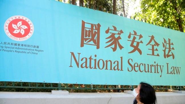 香港一名妇女走过街头的国安法宣传牌(美联社2020年6月30日)