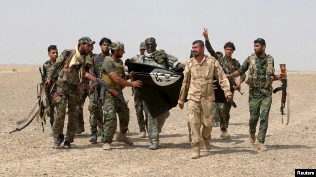 Lực lượng bán quân sự Shia và các thành viên của lực lượng an ninh Iraq kéo cờ của Nhà nước Hồi giáo xuống ở thị trấn Nibai trong tỉnh Anbar, ngày 26/5/2015.