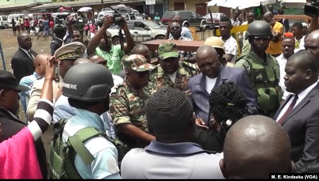 Governor Bernard Okalia Bilai guarded by military pleads with people not to leave, assuring them of their safety.