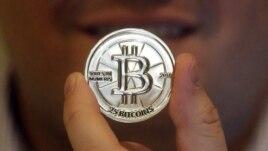 FILE - Mike Caldwell, a 35-year-old software engineer, holds a 25 Bitcoin token at his shop in Sandy, Utah.  Kỹ sư phần mềm Mike Caldwell cầm một đồng 25 bitcoin tại cửa hàng của ông ở Sandy, Utah