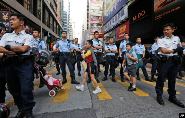 FILE - Students walk across the road on their way to school after police moved in the occupied area in the Mong Kok district of Hong Kong, Friday on Oct. 17, 2014.