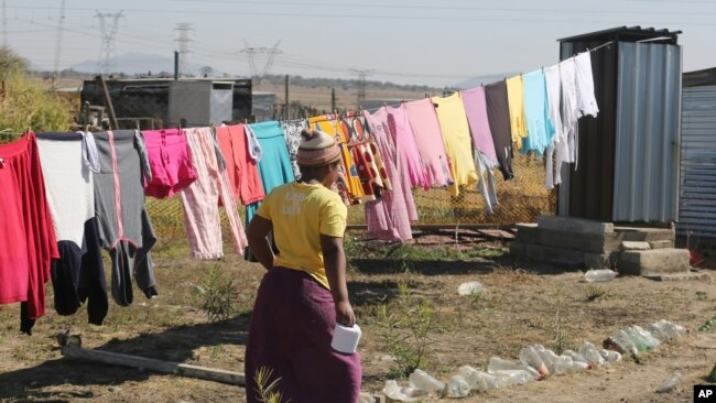 FILE - A woman heads to an outside pit toilet where she shares a shack housing five people, in Marikana, South Africa, Aug. 12, 2016.