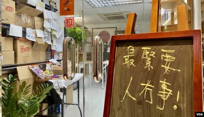 """石墙花位于荔枝角的办公室门外,放有写上""""最紧要人冇事""""(最重人没事)的黑板 (美国之音/汤惠芸)"""