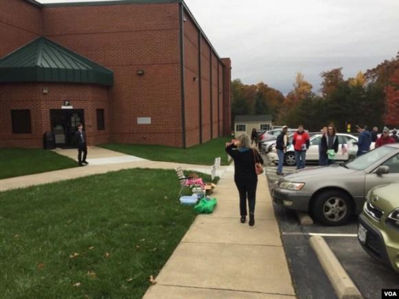 Una votante se acerca al centro electoral en una iglesia del Norte de Virginia, mientras representantes de las campañas republicana y demócrata al fondo esperan para guiar a los electores sobre sus candidatos. Foto: L.Bonett/VOA. Nov. 7, 2017.