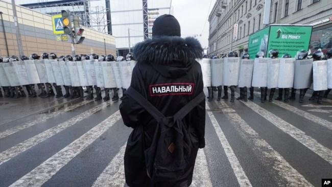 一名阿列克谢·纳瓦尔尼的支持者站在防暴警察前,抗议俄罗斯将纳瓦尔尼判决入狱。(2021年1月31日)