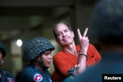FILE - Australian filmmaker James Ricketson gestures as he leaves the Municipal Court of Phnom Penh, Cambodia, Aug. 16, 2018.