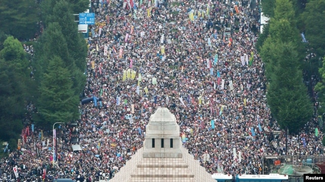 Người dân giơ áp phích và hô vang khẩu hiệu trong cuộc biểu tình phản đối dự luật an ninh của Thủ tướng Abe bên ngoài quốc hội ở Tokyo, 30/8/2015. Ảnh: REUTERS/Kyodo