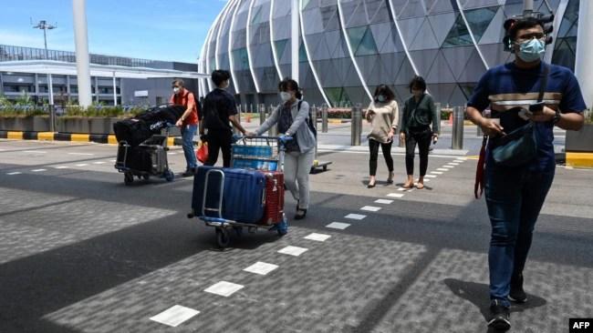 旅客们推着行李进入新加坡樟宜机场的离境大厅。(2021年8月19日)