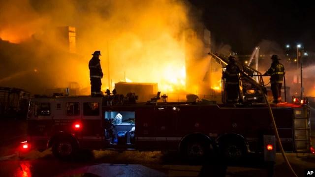Nhân viên cứu hoả cố gắng dập tắt ngọn lửa sau khi người biểu tình đốt một hiệu dược phẩm, đốt xe cảnh sát và ném gạch vào cảnh sát, 27/4/15