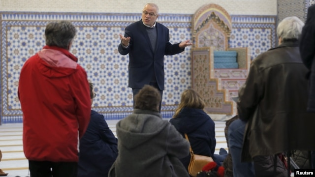 People listen to the explanations of guide Mohamed Latahi (C), as they visit the Strasbourg Grand Mosque during an open day weekend for mosques in France, Jan. 9, 2016.