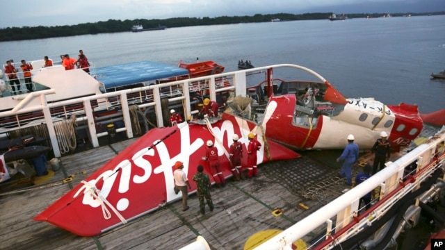 Crew members of Crest Onyx ship prepare to unload parts of AirAsia Flight 8501 from a ship at Kumai port in Pangkalan Bun, Jan.11, 2015.