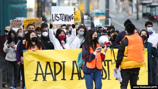 """西雅图示威人士举着""""我们不会沉默""""横幅,抗议针对亚裔的仇视犯罪。(AFP照片)"""