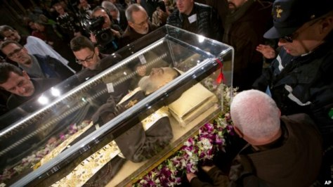 People stand around the mortal remains of Saint Pio (Padre Pio) as they are displayed in Rome's San Lorenzo Basilica, as part of the Roman Catholic Church 2016 Holy Year celebrations, Feb. 3, 2016.