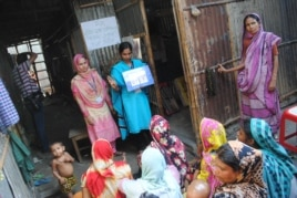 Health workers lecture about reproductive health to volunteers in a slum in Dhaka. (Amy Yee for VOA News)