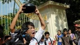 Một sinh viên biểu tình trước cổng Đại học Yangon cầm một cái bát úp, biểu tượng của sự chống đối ở Myanmar, Yangon, Myanmar, ngày 15 tháng 11, 2014. (Steve Herman/VOA )