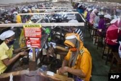 Buruh melinting tembakau di terminal kerja mereka, dipisahkan oleh penutup plastik sebagai bagian dari tindakan di tengah pandemi virus Covid-19, di pabrik rokok Gudang Baru di Malang, Jawa Timur, pada 11 Juli 2020. (Foto: AMAN ROCHMAN / AFP)