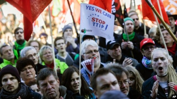 A man blows a whistle during a massive demonstration against the free trade agreements TTIP (Transatlantic Trade and Investment Partnership) and CETA (Comprehensive Economic and Trade Agreement) in Berlin, Oct. 10, 2015.