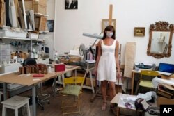 Emmanuelle Prevot, working as restorer of paintings and art creations poses in her painting workshop in Paris, Tuesday, July 21, 2020. Emmanuelle said that she does not wear a mask always while working with chemicals for paintings.