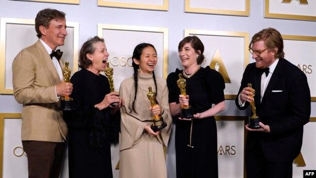 2021年4月25日获得奥斯卡最佳导演奖的赵婷(中)与其最佳影片《无依之地》的其他获奖人员在一起。(法新社)
