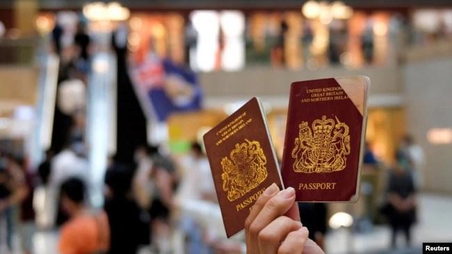 资料照:一名香港示威者在反对港版国安法的抗议中手举英国国民海外护照。(2020年6月1日)