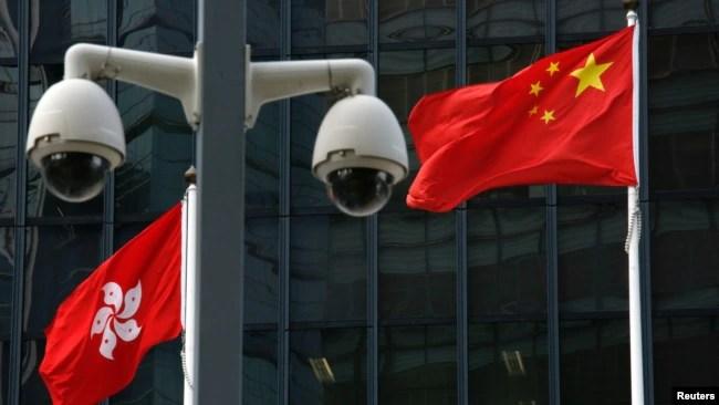 资料照:在香港政府总部大楼外监控摄像头后的中国国旗和香港特区旗帜。