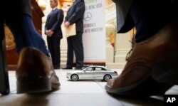 FILE- A Mercedes-Benz model sits in front of Robert Moran, director of communications for Mercedes-Benz USA, during a ceremony announcing the company's relocation of its U.S. corporate headquarters to the metro Atlanta city of Sandy Springs, Feb. 3, 2015.