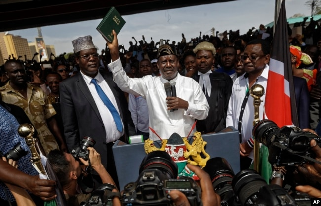 "FILE - Opposition leader Raila Odinga (C) accompanied by lawyers Miguna Miguna (C-L), Tom ""T.J."" Kajwang, (C-R) and politician James Orengo (R) holds a bible aloft after swearing an oath during a mock ""swearing-in"" ceremony at Uhuru Park in downtown Nairobi, Kenya, Jan. 30, 2018."