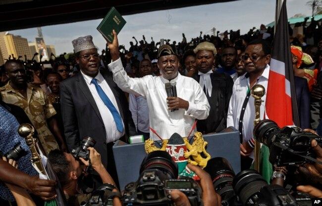 "FILE - Opposition leader Raila Odinga (C) accompanied by lawyers Miguna Miguna (C-L), Tom ""T.J."" Kajwang, (C-R) and politician James Orengo (R) holds a bible aloft after swearing an oath during a mock ""swearing-in"" ceremony at Uhuru Park in downtown Nairobi, Kenya, Jan. 30, 2018."
