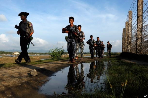 Myanmar police officers patrol along the fence bordering Bangladesh in Maungdaw, Rakhine State, Myanmar, Oct. 14, 2016. New reports accuse soldiers of brutality against Myanmar's long-persecuted Rohingya Muslims.