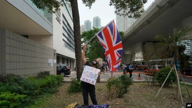 一位民主派支持者于2021年4月16日在香港法庭外挥舞英国国旗。包括82岁的香港民主党创建人李柱铭和支持民主的媒体大亨黎智英在内的七位香港主要的民主派人士因参与2019年8月的一次集会,被控参与未经授权的集结罪名。周五法官对七人做出宣判。