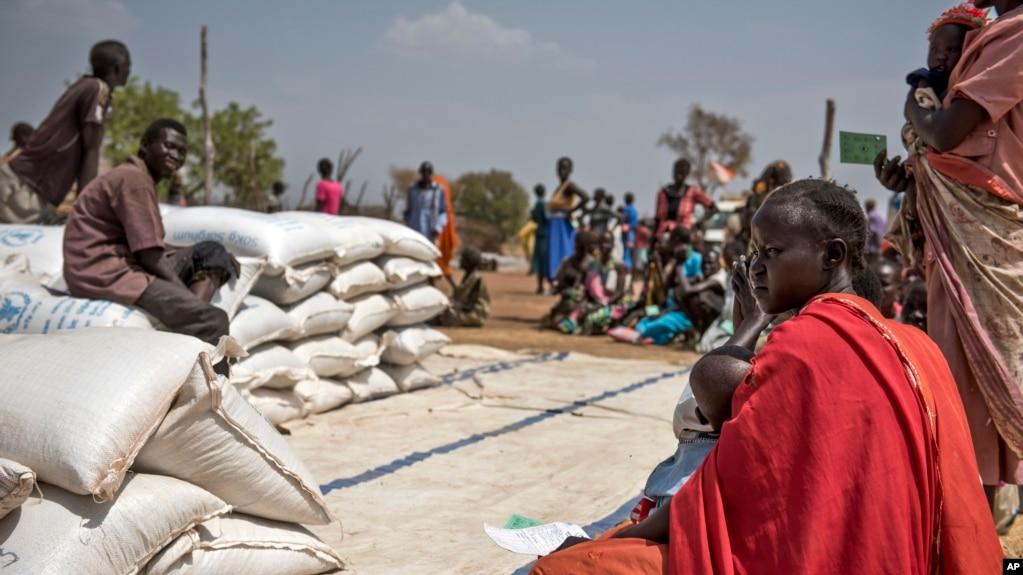 FILE - People wait to receive food at a World Vision food distribution site in Malualkuel in the Northern Bahr el Ghazal region of South Sudan, April 5, 2017.