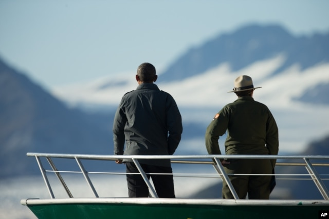 President Barack Obama, accompanied by a National Park Service employee looks at Bear Glacier, which has receded 1.8 miles in approximately 100 years, while on a boat tour to see the effects of global warming in Resurrection Cove, Sept. 1, 2015.