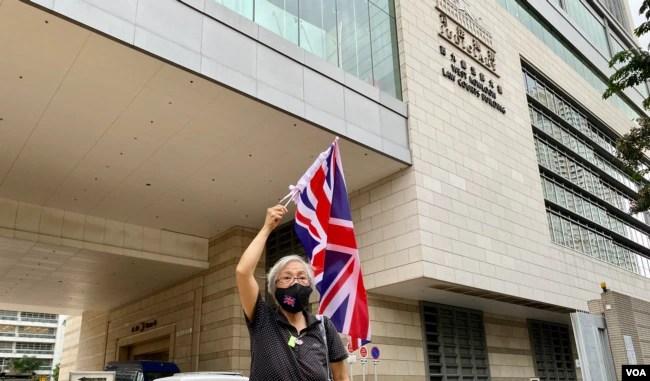 香港社运人士王婆婆9月23日在西九龙裁判法院大楼外,高举英国旗声援民主派初选47人案的被告 (美国之音/汤惠芸)