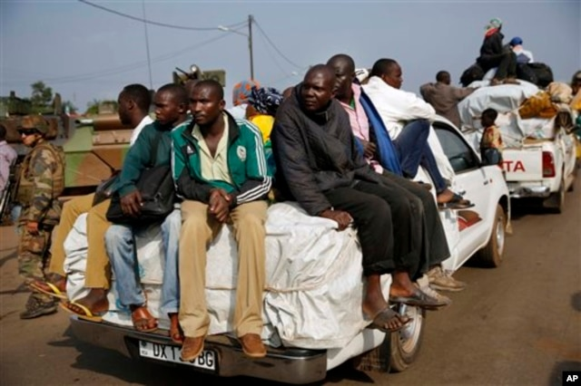 FILE - At PK12, the last checkpoint at the exit of the town, thousands of Muslim residents from Bangui and Mbaiki flee the Central African Republic capital Bangui in a mass exodus using cars, pickups, trucks, lorries and motorcycles, escorted by Chadian troops,