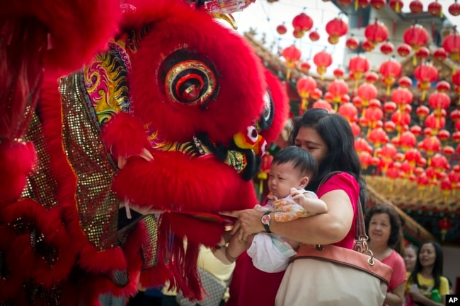 FILE - A Malaysian woman and her child give red packet to the lion dance troupe during the lion dance performance on the first day of Chinese Lunar New Year at a temple in Kuala Lumpur, Malaysia on Thursday, Feb. 19, 2015.