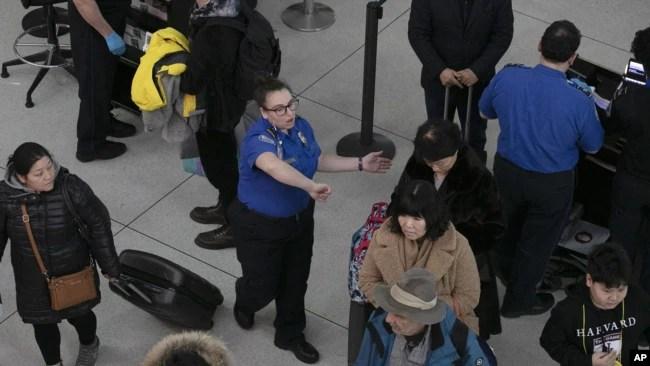 Un agente de la TSA, centro, dirige a los pasajeros a través de un punto de control de seguridad, el lunes 7 de enero de 2019, en el Aeropuerto Internacional John F. Kennedy de Nueva York. El líder de la minoría del Senado, Chuck Schumer, demócrata por Nueva York, sugirió el domingo que el cierre parcial del gobierno está interrumpiendo las operaciones de la Administración de Seguridad del Transporte.