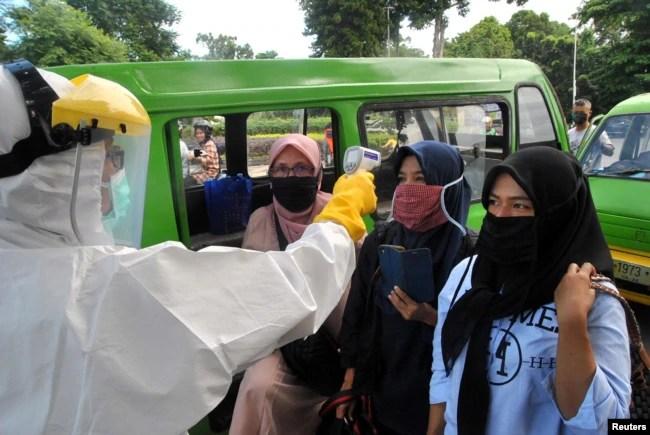 Para penumpang angkutan umum mengenakan masker wajah sedang diperiksa suhu oleh petugas kesehatan di tengah penyebaran wabah virus corona (Covid-19), di Bogor, Jawa Barat, 8 April 2020.