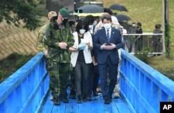 Menteri Unifikasi Korea Selatan Lee In-young (kanan), berjalan di jembatan biru saat berkunjung ke Panmunjom di Zona Demiliterisasi, Korea Selatan, Rabu, 16 September 2020.