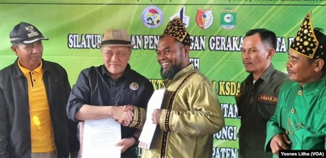 Penjabat Dirjen Konservasi Sumber Daya Alam dan Ekosistem (KSDAE) Wiratno dan Ketua Forum Petani Merdeka (FPM) Dongi-Dongi berjabat tangan seusai penandatangan kesepakatan bersama dalam upaya pelestarian Taman Nasional Lore Lindu, 2 Agustus 2019. (Foto: