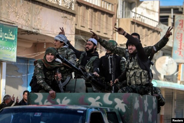 FILE - Fighters of the Kurdish People's Protection Units (YPG) carry their weapons along a street in the Syrian Kurdish city of Qamishli, in celebration after it was reported that Kurdish forces took control of the Syrian town of Tel Hamis, Feb. 27, 2015.