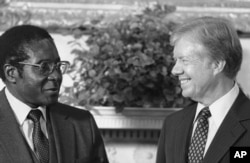 FILE: President Jimmy Carter meets up Zimbabwe Prime Minister Robert Mugabe in the Oval Office in Washington on August 27, 1980. (AP Photo/Barry Thumma)