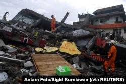 Tim SAR memeriksa bangunan yang roboh akibat guncangan gempa di Mamuju, Sulawesi Barat, Sabtu, 16 Januari 2021. (Foto: Antara Foto/Sigid Kurniawan via Reuters)