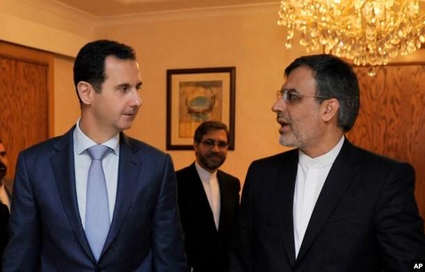 Syrian President Bashar al-Assad, left, meets with Iranian Deputy Foreign Minister for Arab-African Affairs Hossein Jaberi Ansari in Damascus, Syria, Thursday, Dec. 22, 2016.