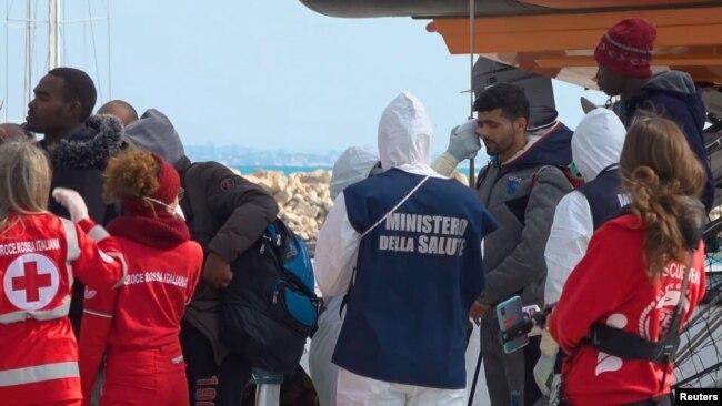 Un funcionario médico con un traje de protección debido al brote de coronavirus, verifica la temperatura de un migrante que desembarca del barco de rescate 'Open Arms' en Pozzallo, Italia, el 2 de febrero de 2020.