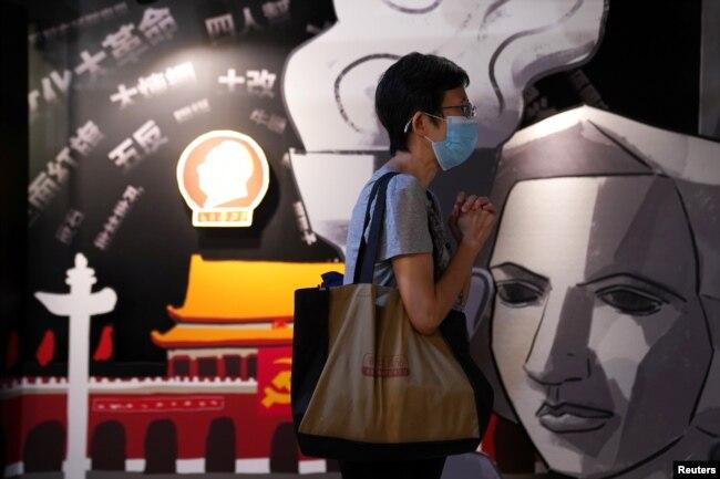 资料照:香港支联会营运的六四纪念馆里一名遊客在一块刻有民主女神像的板子旁祈祷。
