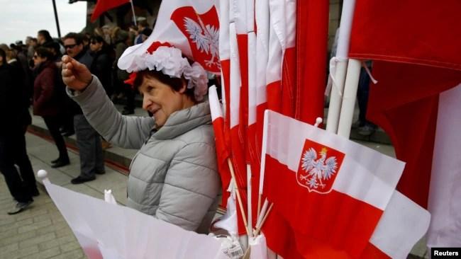 华沙街头一名小贩出售带有国徽的波兰国旗庆祝该国的宪法日。(2017年5月3日)