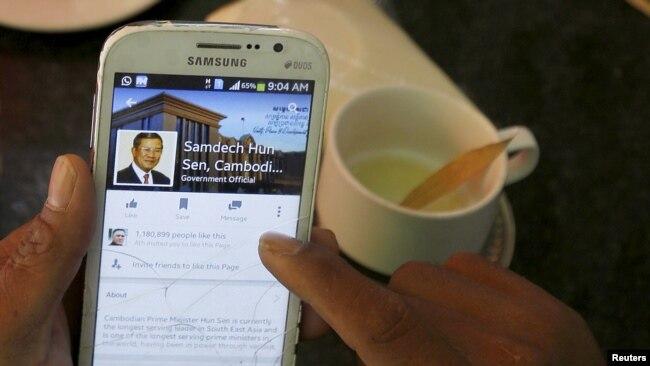 资料照片-在柬埔寨金边市中心的一家餐厅吃早餐时,一名男子用智能手机查看柬埔寨首相洪森的脸书主页。(2015年10月7日)